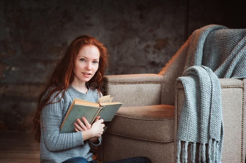 Het gelukkige roodharigevrouw ontspannen thuis in comfortabel de winter of de herfstweekend met boek en kop die van hete thee, al stock foto