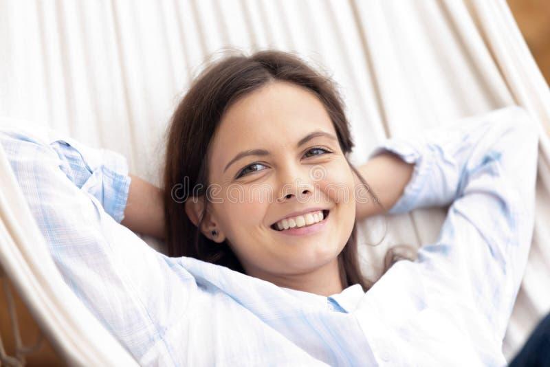 Het gelukkige rustige wijfje ligt in hangmat die in openlucht rusten stock foto