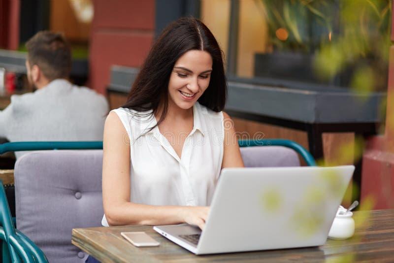 Het gelukkige schitterende jonge wijfje met lang recht donker haar, heeft prettige glimlach, intikt iets op laptop computer, binn royalty-vrije stock afbeelding