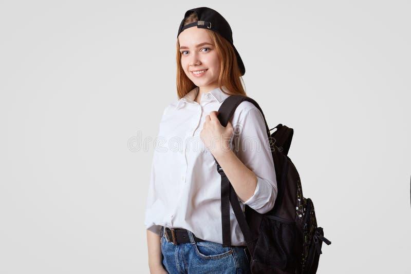 Het gelukkige schoolmeisje in zwart GLB en wit overhemd, draagt rugzak met boeken, klaar voor beginnend nieuw het bestuderen jaar royalty-vrije stock fotografie