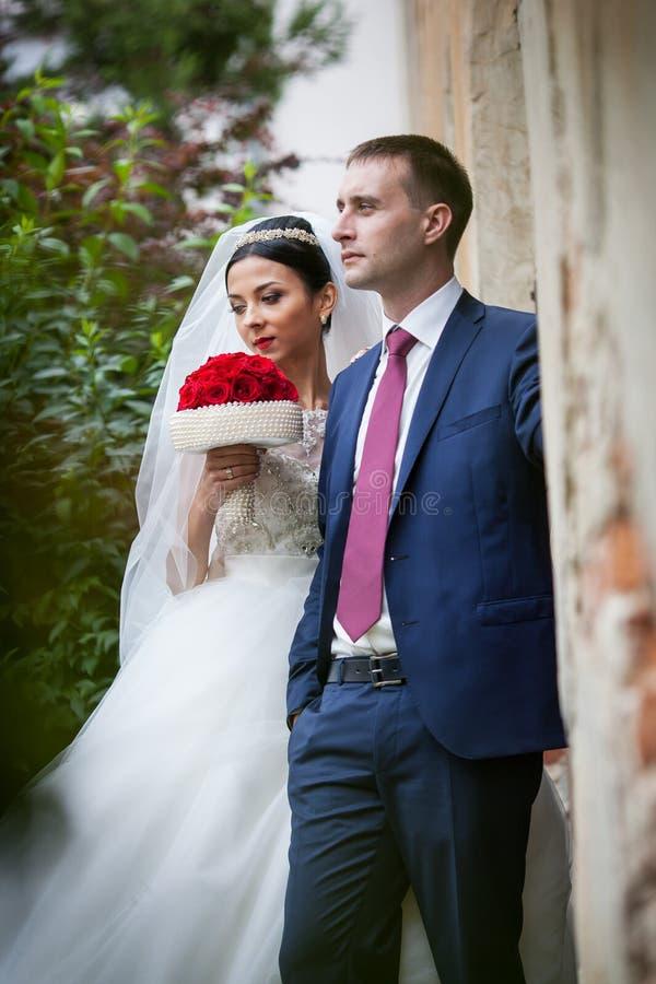 Het gelukkige sensuele van de jonggehuwdeechtgenoot en vrouw stellen dichtbij de oude bouw stock fotografie