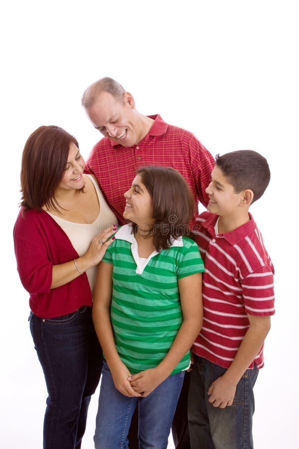 Het gelukkige Spaanse familie koesteren geïsoleerd op wit stock afbeelding