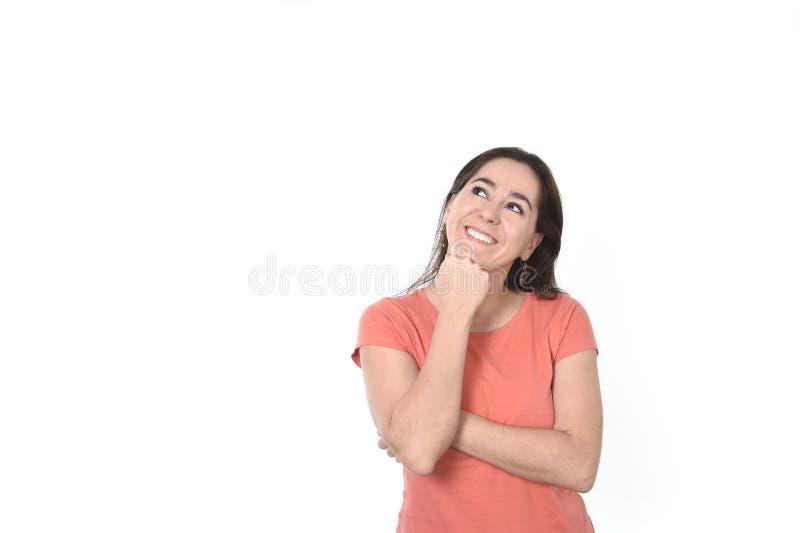 Het gelukkige Spaanse vrouw nadenkende en peinzende denken en het dromen kijken omhoog glimlachend op exemplaarruimte stock foto