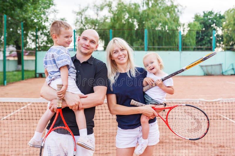 Het gelukkige speeltennis van het familieportret in openlucht en glimlachend royalty-vrije stock foto's