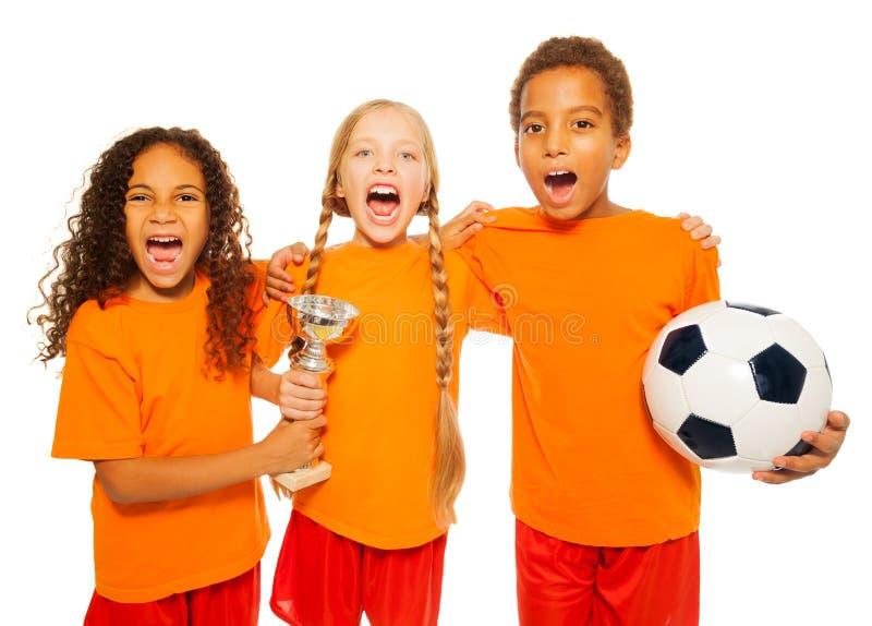 Het gelukkige spel van het voetbalteam met prijskop het gillen stock foto's