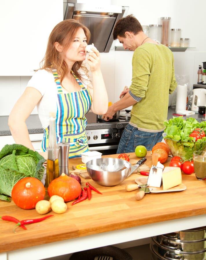 Het gelukkige sportieve paar bereidt gezond voedsel op lichte keuken voor stock foto's