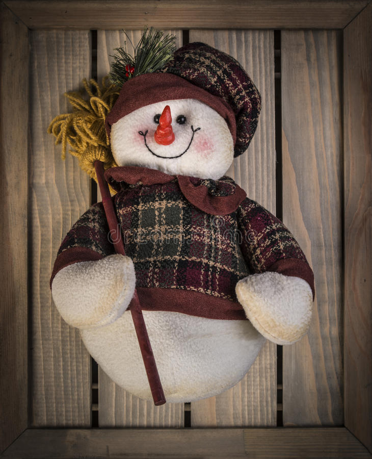 Het gelukkige stuk speelgoed van de sneeuwmanpluche met een bezem en geklede warm, over houten textuurachtergrond royalty-vrije stock foto's