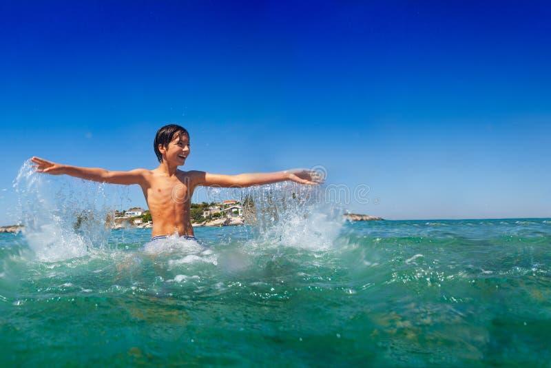 Het gelukkige tiener spelen in water bij de kust stock afbeeldingen