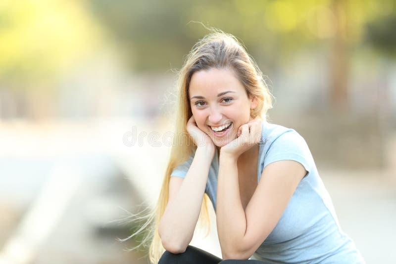 Het gelukkige tiener stellen die camera in een park bekijken stock afbeelding