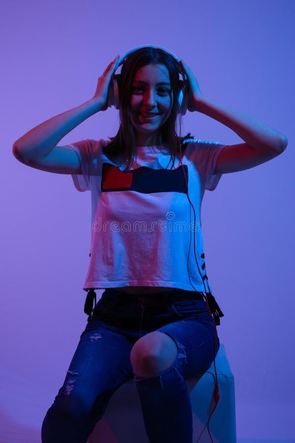 Het gelukkige tienermeisje luistert aan muziek en houdt grote hoofdtelefoons op hoofd en de tanden glimlachen op gezicht royalty-vrije stock afbeelding