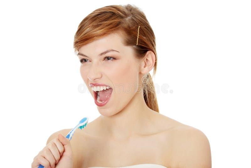 Het gelukkige tienermeisje zingen aan tandenborstel stock foto's