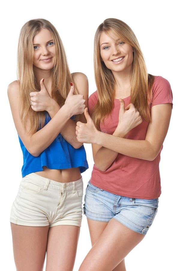 Het gelukkige twee meisjesvrienden gesturing beduimelt omhoog stock afbeeldingen