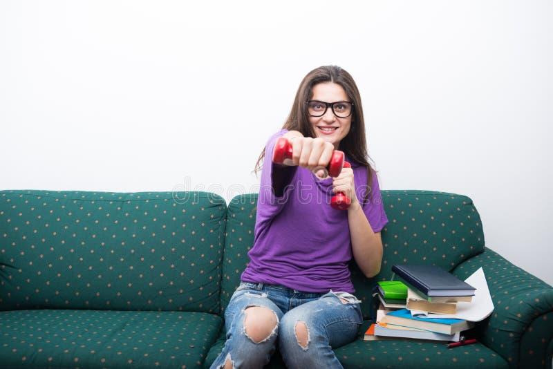 Het gelukkige universiteitsmeisje doen oefent thuis uit stock foto