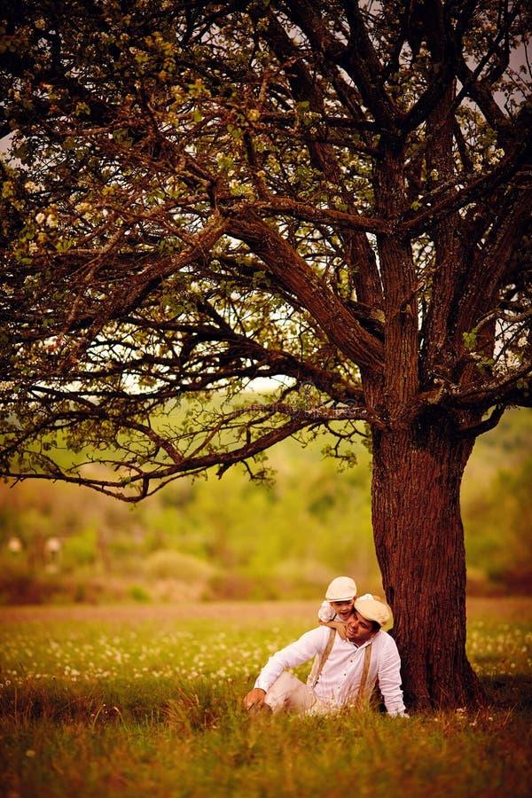Download Het Gelukkige Vader En Zoons Spelen Samen Onder Een Oude Boom Stock Foto - Afbeelding bestaande uit gras, landbouwer: 54091134