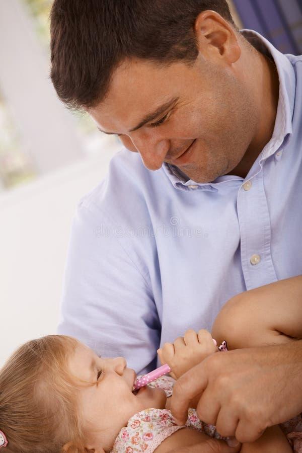 Het gelukkige vader spelen met weinig dochter het glimlachen stock foto