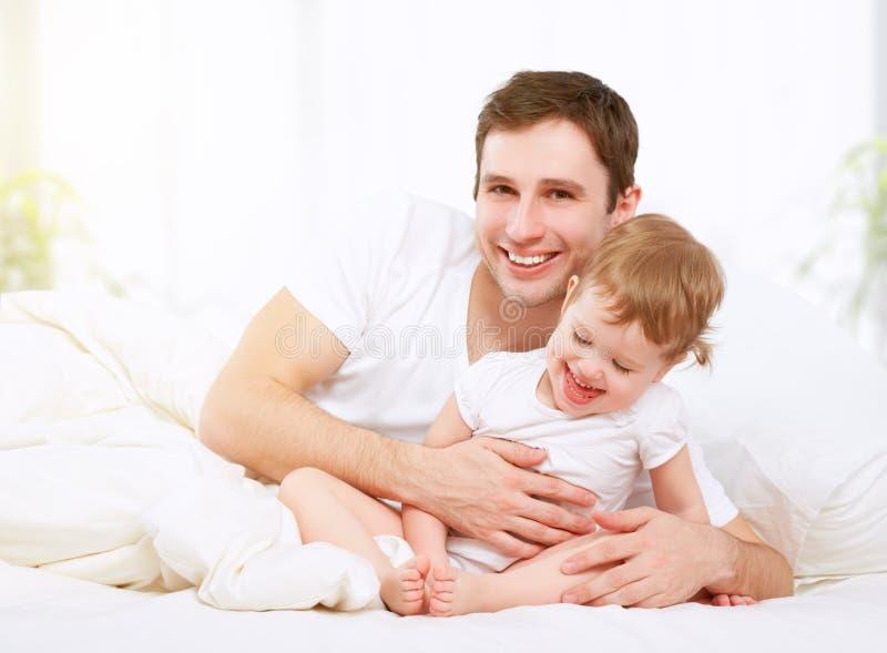 Het gelukkige van de familievader en baby dochter spelen in bed royalty-vrije stock afbeeldingen