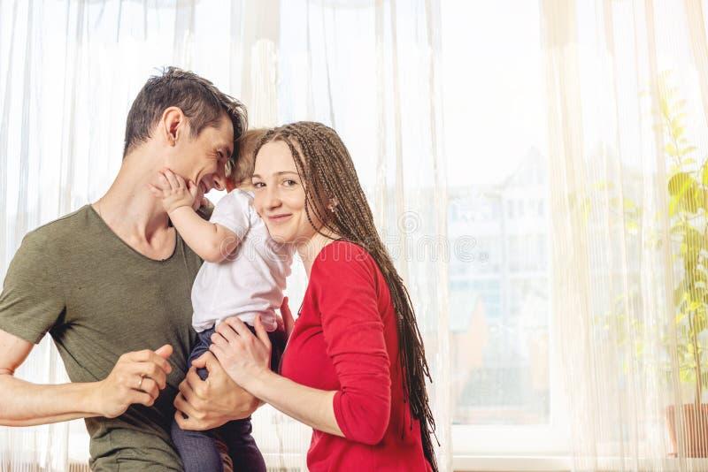 Het gelukkige van de oudersvader en moeder spelen met babyzoon bij de binnen ochtend op vensterachtergrond Vrolijke jonge familie royalty-vrije stock fotografie