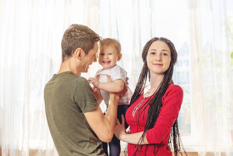 Het gelukkige van de oudersvader en moeder spelen met babyzoon bij de binnen ochtend op vensterachtergrond Vrolijke jonge familie stock afbeelding