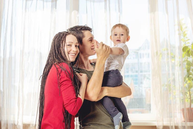 Het gelukkige van de oudersvader en moeder spelen met babyzoon bij de binnen ochtend Vrolijke en moderne jonge familie stock afbeeldingen