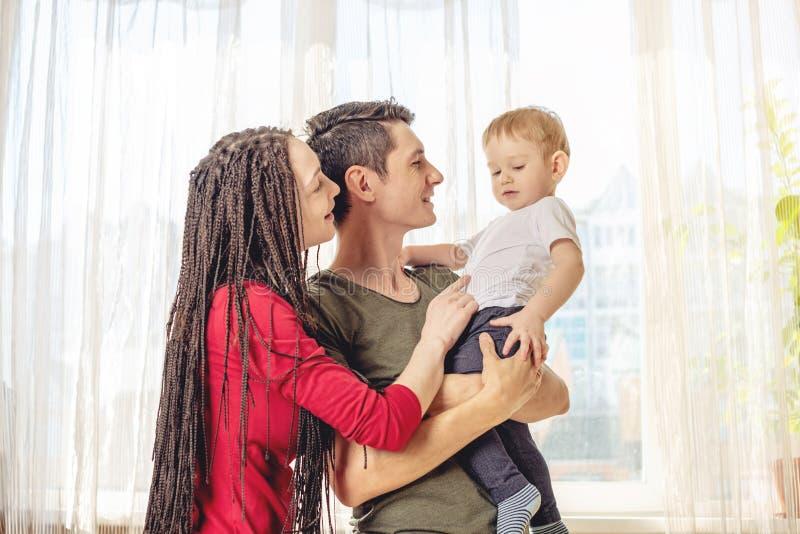 Het gelukkige van de oudersvader en moeder spelen met babyzoon bij de binnen ochtend Vrolijke en moderne jonge familie stock fotografie
