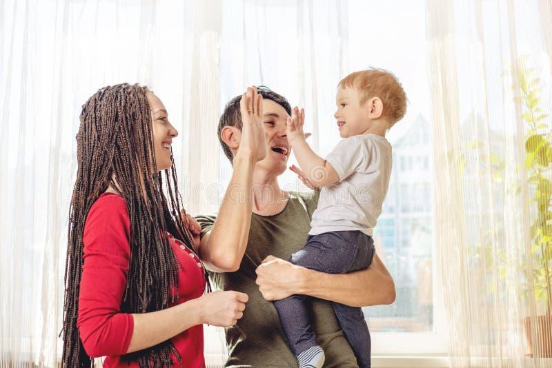 Het gelukkige van de oudersvader en moeder spelen met babyzoon bij de binnen ochtend Vrolijke en moderne jonge familie stock foto