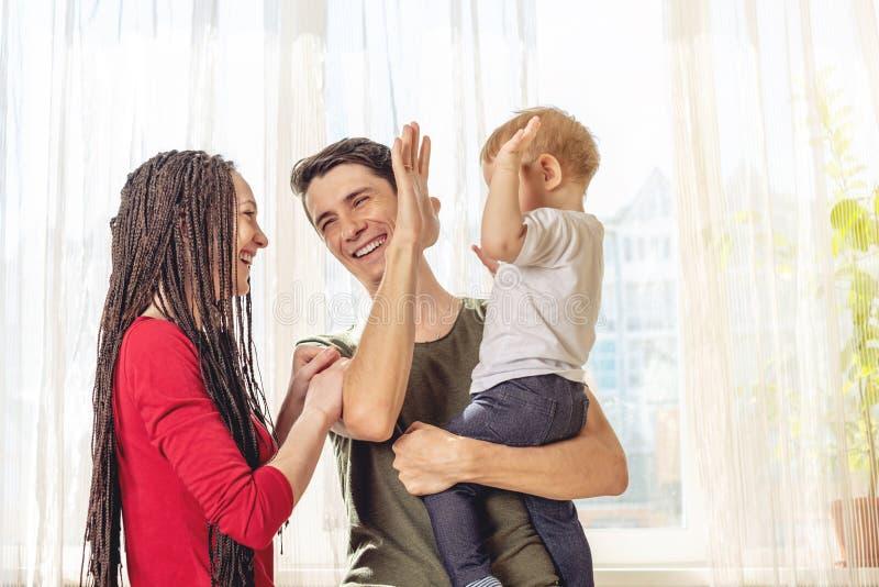 Het gelukkige van de oudersvader en moeder spelen met babyzoon bij de binnen ochtend Vrolijke en moderne jonge familie royalty-vrije stock foto's