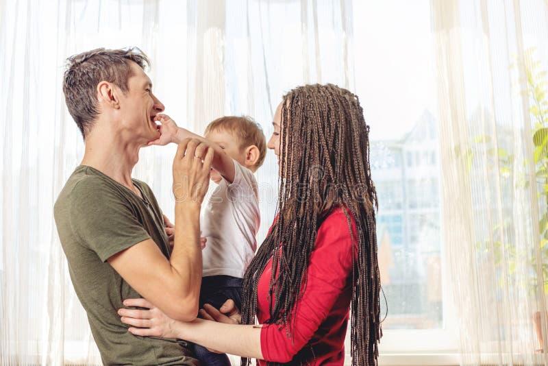 Het gelukkige van de oudersvader en moeder spelen met babyzoon bij de binnen ochtend Vrolijke en moderne jonge familie royalty-vrije stock foto