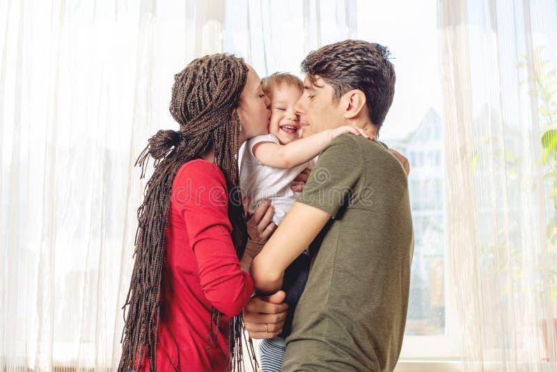 Het gelukkige van de oudersvader en moeder spelen met babyzoon bij de vensterachtergrond Vrolijke en moderne jonge familie royalty-vrije stock foto's