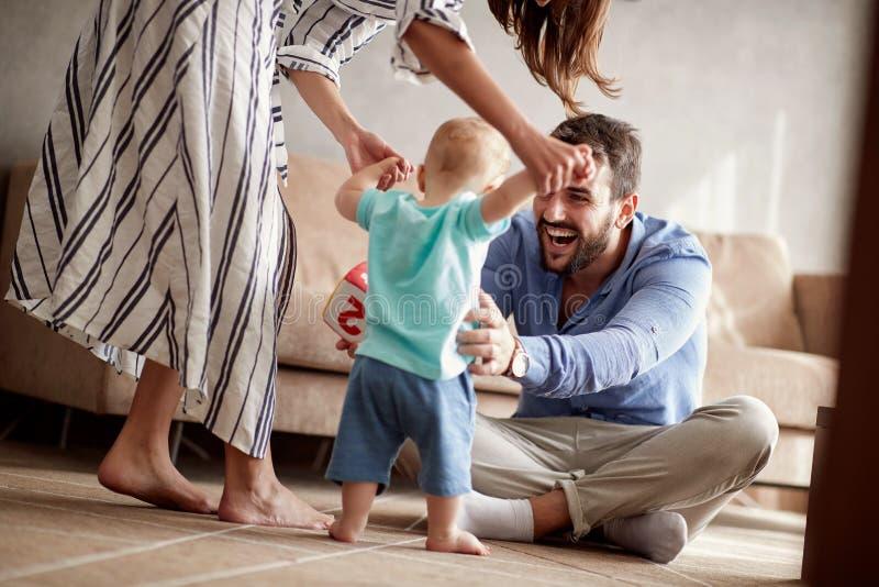 Het gelukkige van de paarmoeder en vader spelen met een baby thuis stock afbeeldingen