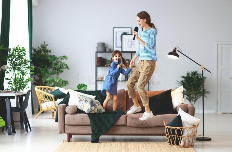 Het gelukkige van het familiemoeder en kind spel thuis en zingt met kammen royalty-vrije stock fotografie