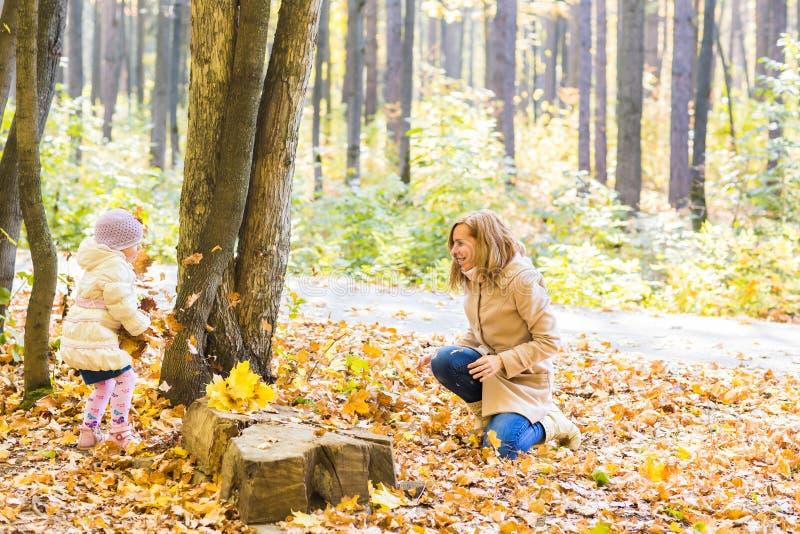Het gelukkige van het familiemoeder en kind meisje spelen werpt bladeren in openlucht in de herfstpark stock fotografie