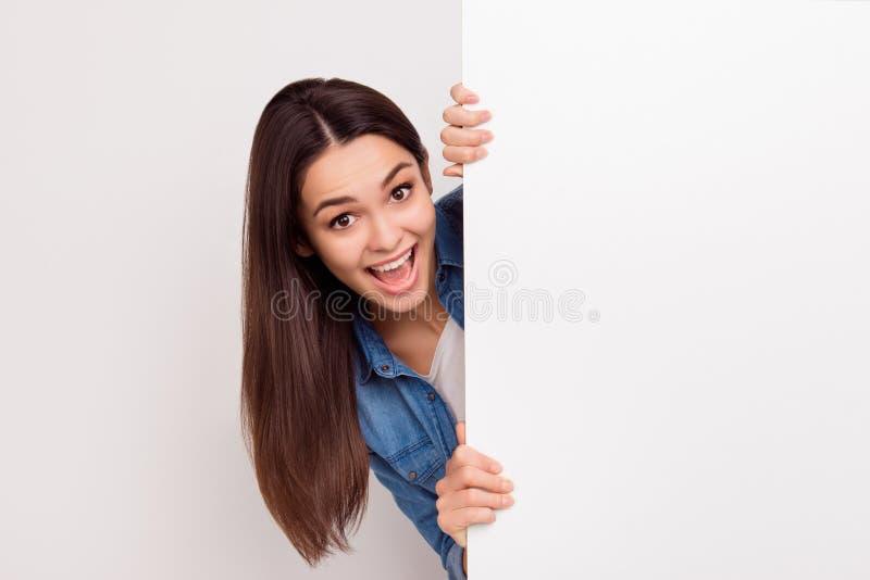 Het gelukkige verbaasde jonge meisje knalt uit van witte lege banner royalty-vrije stock fotografie
