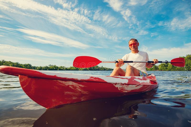 Het gelukkige volwassen mens kayaking op de rivier bij een zonnige ochtend royalty-vrije stock fotografie