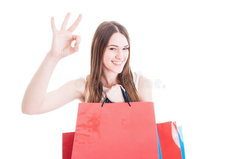 Het gelukkige vriendschappelijke meisje doen winkelend en tonend o.k. teken royalty-vrije stock fotografie