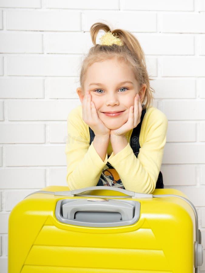 Het gelukkige vrolijke meisje van de kindtoerist met een gele koffer voor het reizen, ontspannend, glurend binnen een zak en het  royalty-vrije stock foto's