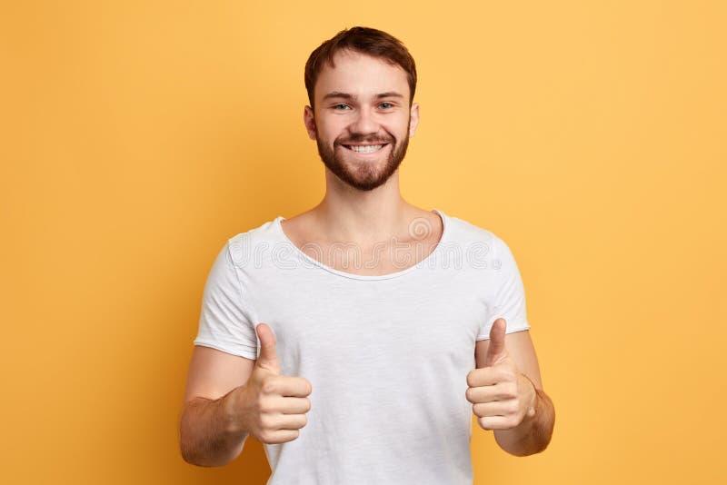 Het gelukkige vrolijke mens geven beduimelt omhoog sluit omhoog portret op gele achtergrond stock foto's