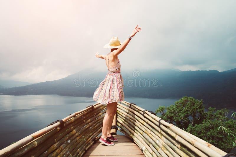 Het gelukkige vrouw het dansen vrij voelen reizend de wereld die wapens opheffen aan de hemel stock foto