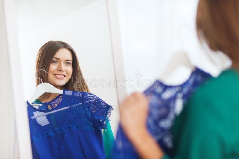 Het gelukkige vrouw kiezen kleedt thuis garderobe stock afbeelding