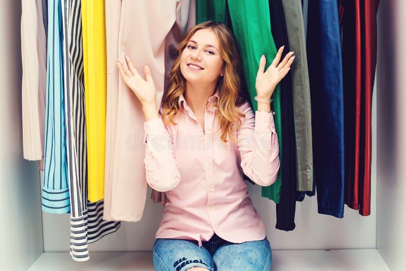 Het gelukkige vrouw kiezen kleedt thuis garderobe Harde keus Kleding, manier, levensstijl en mensenconcept De vrouwen vormen wink royalty-vrije stock foto