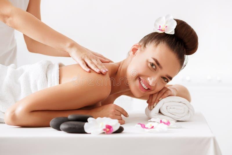 Het gelukkige vrouw krijgen ontspant massage in kuuroordcentrum royalty-vrije stock foto's