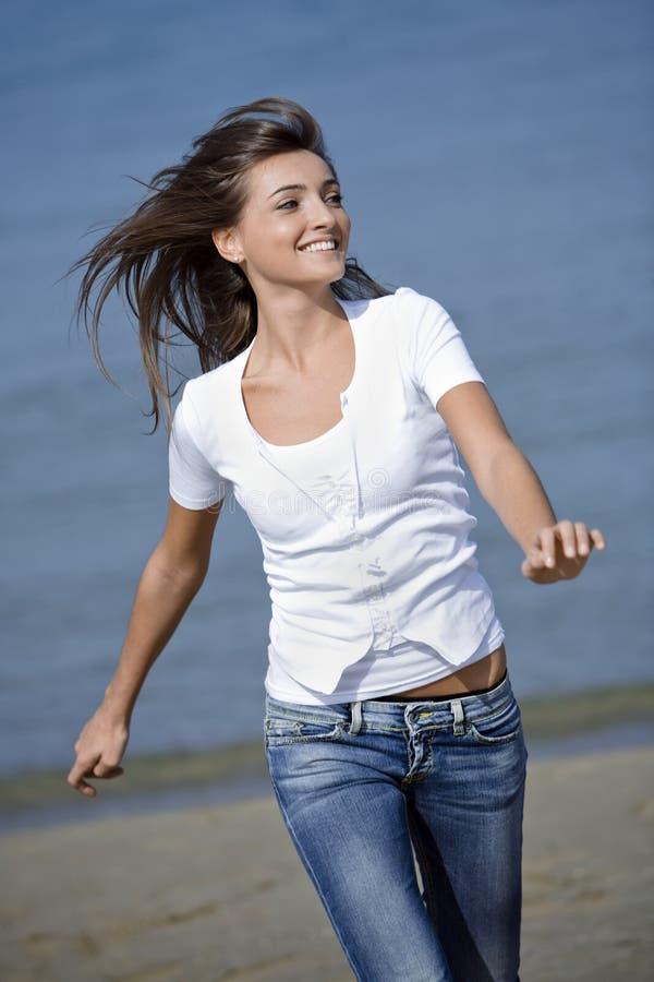 Het gelukkige vrouw lopen windblown op het strand royalty-vrije stock foto