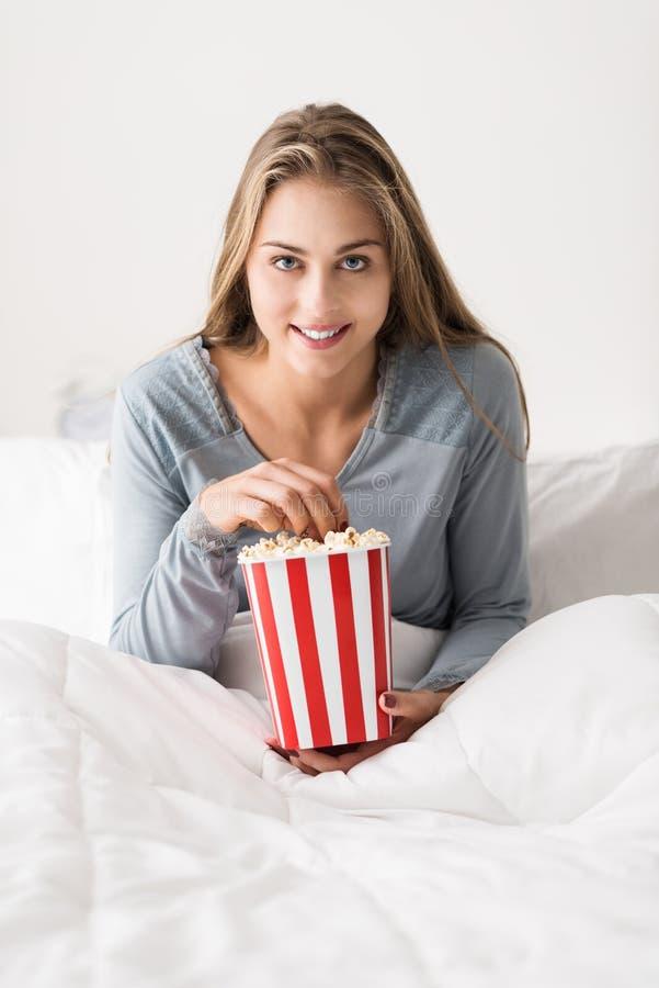 Het gelukkige vrouw ontspannen in bed stock afbeelding