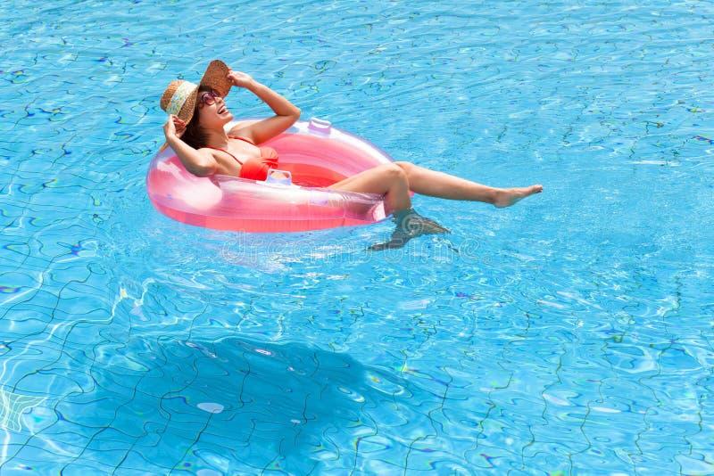 Het gelukkige vrouw ontspannen in zwembad stock foto's