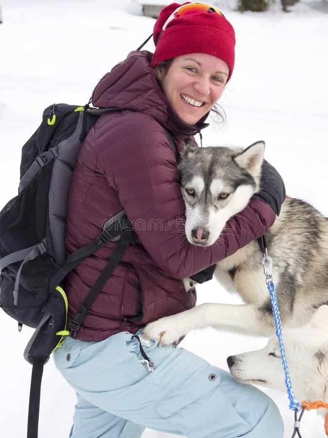 Het gelukkige vrouw spelen met sleehond in sneeuw stock afbeeldingen