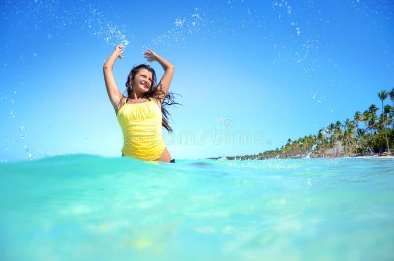 Het gelukkige vrouw spelen met water op exotisch strand stock foto's