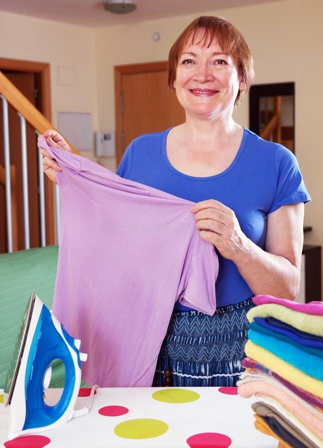 Het gelukkige vrouw strijken stock afbeelding