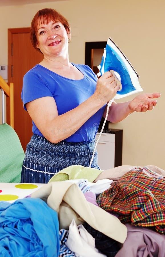 Het gelukkige vrouw strijken stock foto