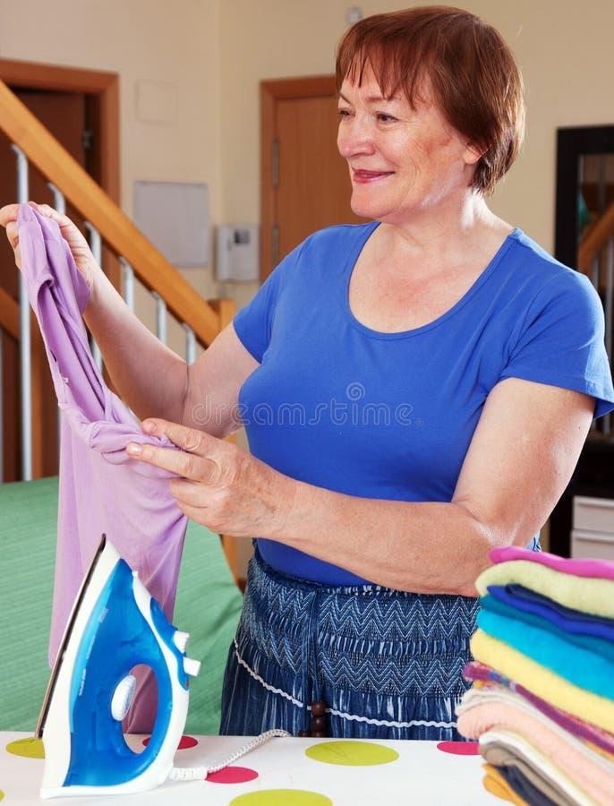 Het gelukkige vrouw strijken stock fotografie