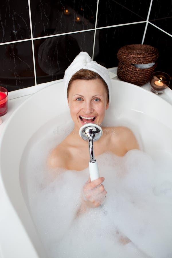 Het gelukkige vrouw zingen in een schuimbad stock afbeeldingen