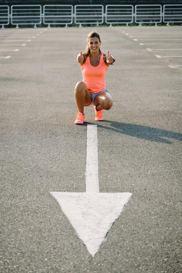 Het gelukkige vrouwelijke atleet doen beduimelt omhoog succesgebaar stock fotografie
